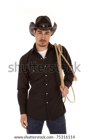 A cowboy is standing with a serious expression holding a rope over his shoulder
