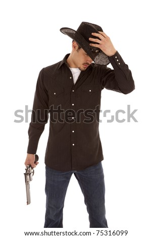 A cowboy is standing with his hand on his hat and a gun in the other hand. - stock photo