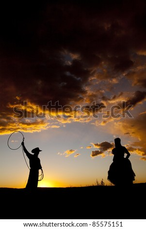A cowboy is swinging a rope and a woman watching in the sunset.