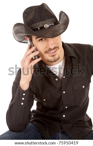 A cowboy is talking on the phone and smiling. - stock photo
