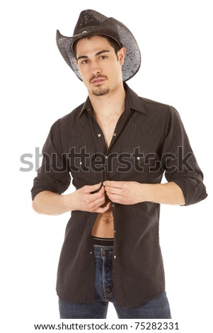 A cowboy is wearing a black shirt doing up the buttons - stock photo
