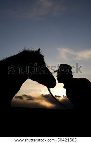 A cowboy kissing his horse in the sunset