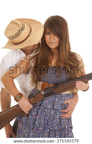 A cowboy leaning around his woman while she is holding on to a rifle. - stock photo