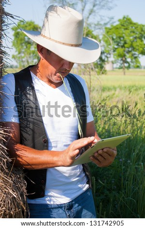 A cowboy leaning on the hay stack in a countryside setting using touchscreen on a tablet computer - stock photo