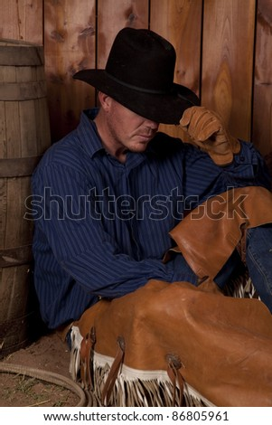 A cowboy leaning up against a wine barrel holding down his hat.
