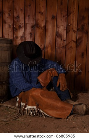 A cowboy leaning up against a wine barrel sitting in the dirt taking a rest