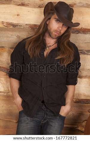 a cowboy leaning up against a wood wall with a serious expression on his face. - stock photo