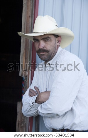 A cowboy leans against a building with his arms crossed. - stock photo