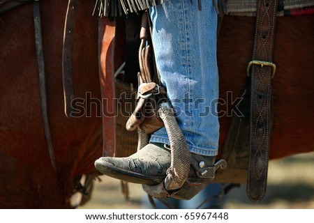 A cowboy leg wearing jeans and a cowboy boot in a stirrup on a horse. - stock photo
