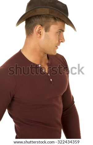 A cowboy looking to the side in his western hat and tight shirt. - stock photo
