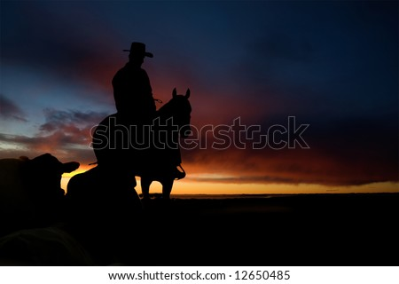 A cowboy on a hill against a sunset - stock photo