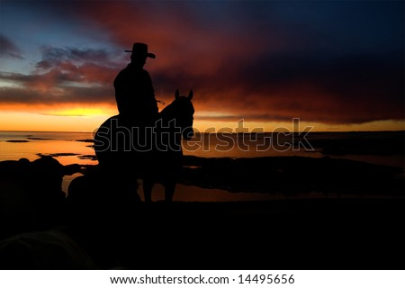 A cowboy on a hill against a sunset and ocean - stock photo
