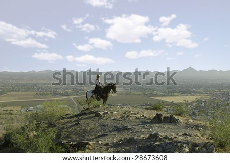 A cowboy overlooking downtown - stock photo