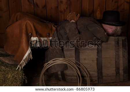 A cowboy resting on top of a wine barrel with his hat on top of his face.