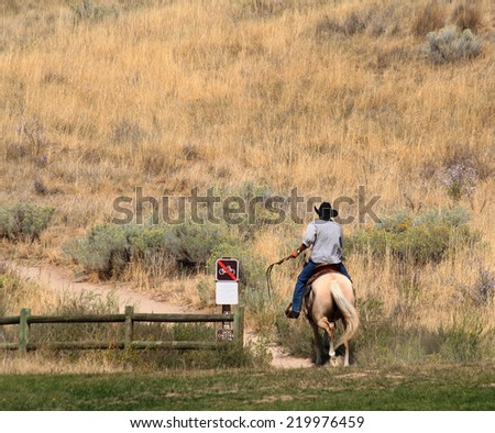 a cowboy riding a horse up a trail in a local public park  - stock photo