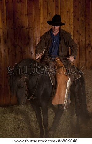 A cowboy riding his horse that is kicking up dust.