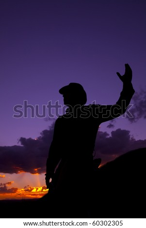 A cowboy riding in the saddle with one hand up. - stock photo