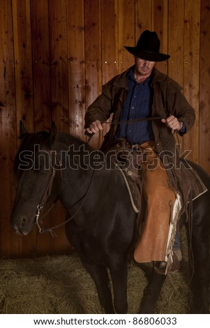 A cowboy riding on his black horse by the hay.