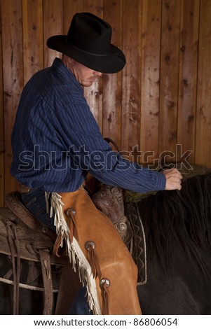 A cowboy riding on his horses back with a serious expression.