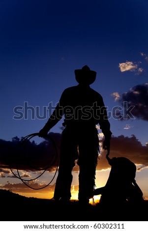 A cowboy silhouetted in the sunset holding a rope and a saddle.