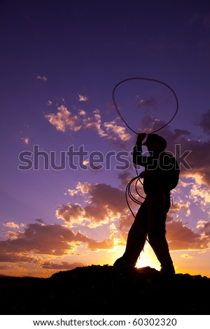 A cowboy silhouetted in the sunset twirling a rope.