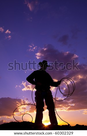 A cowboy silhouetted in the sunset with a rope. - stock photo