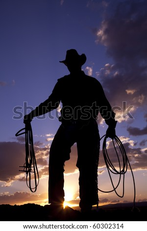 A cowboy  silhoutted by a beautiful sunset holding a rope and a halter. - stock photo