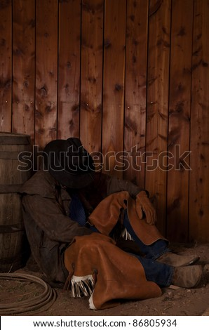 A cowboy sitting in the dirt leaning up against a wine barrel taking a rest.