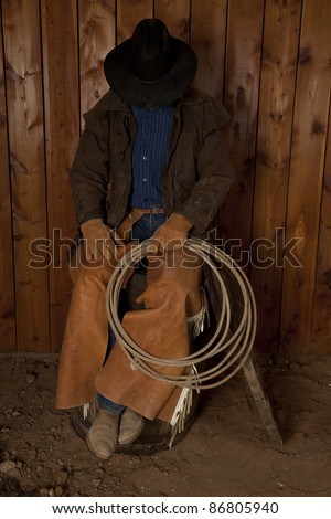 A cowboy sitting on a wine barrel with his head down. - stock photo