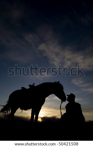 A cowboy sitting on the ground beside his horse. - stock photo