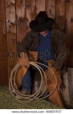 A cowboy sitting on top of a wine barrel with his foot up on top of a hay bale.