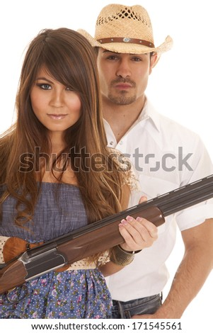 A cowboy standing behind his woman and she is holding the weapon. - stock photo