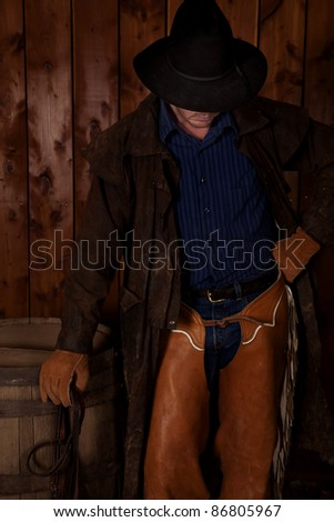 A cowboy standing next to a wine barrel with his fist on his hip holding his reins. - stock photo