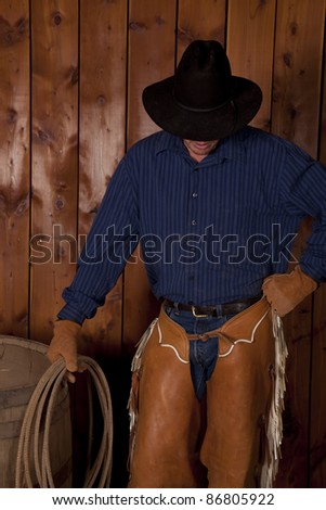 A cowboy standing next to a wine barrel with his head down.