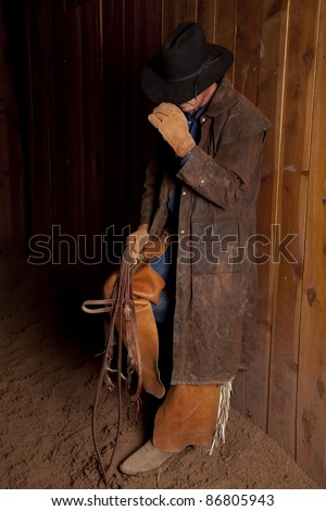 A cowboy standing up against a wall in the dirt with his head down.