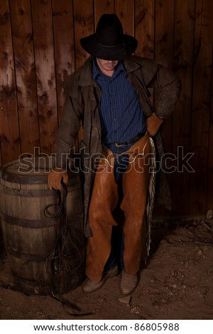 A cowboy standing up in the dirt with his head down. - stock photo