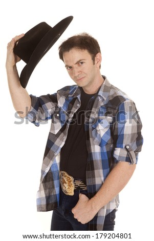 A cowboy standing with a black hat in his hand. - stock photo