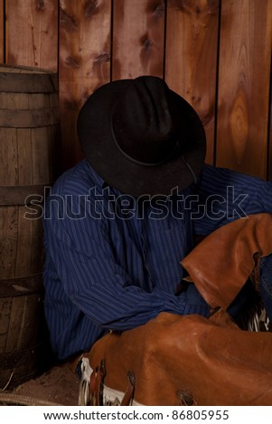 A cowboy taking a rest leaning his back on a wine barrel. - stock photo