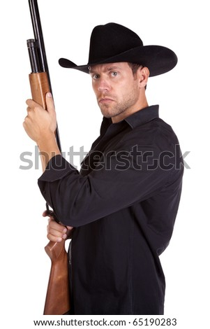 A cowboy with a serious expression on his face holding his rifle. - stock photo