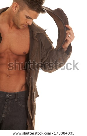 A cowboy with his duster on taking off his cowboy hat. - stock photo
