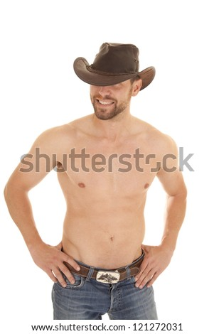 A cowboy with his hands on his hips with a smile on his face. - stock photo