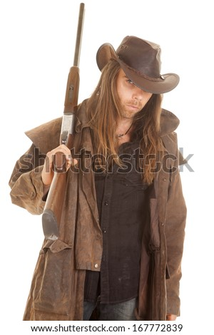 A cowboy with his rifle on his shoulder with a serious expression on his face. - stock photo