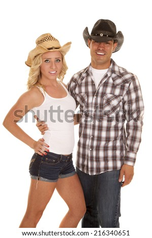 a cowgirl and cowboy with smiles they are holding on to each other. - stock photo