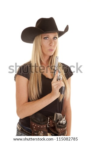 A cowgirl dressed in black holding on to her pistol blowing on the tip of the gun. - stock photo