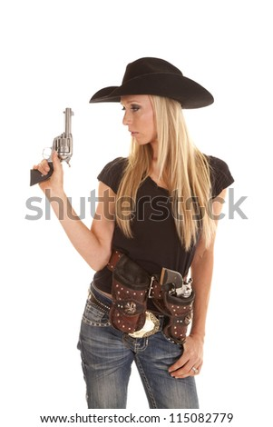 a cowgirl dressed in black holding up her pistol with her other gun in her holster. - stock photo