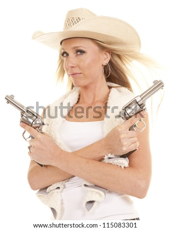 A cowgirl holding on to her two pistols across her chest with a serious expression on her face with the wind blowing her hair. - stock photo