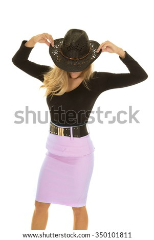 A cowgirl holding on to her western hat looking down.