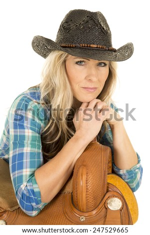 a cowgirl in her blue plaid shirt wearing her black western hat, leaning on a saddle.