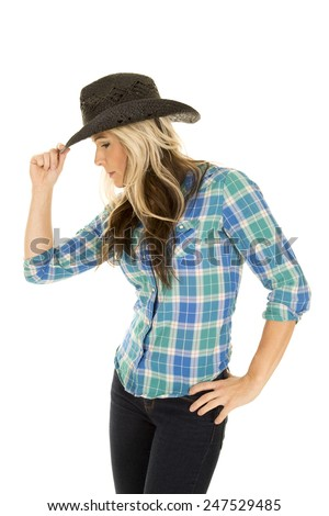 a cowgirl in her blue plaid top touching the brim of her hat looking down. - stock photo