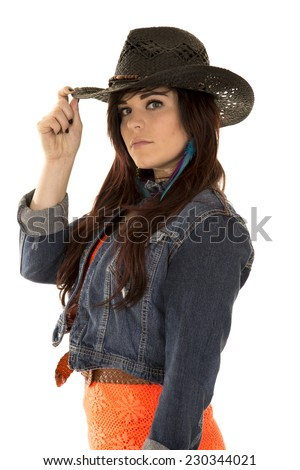 A cowgirl in her cowgirl hat touching the brim of her hat. - stock photo